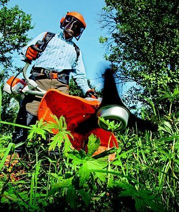 Mężczyzna koszący trawę wykaszarką spalinową